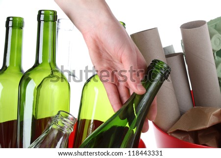 Glass bottles and paper garbage, recycling bin - stock photo