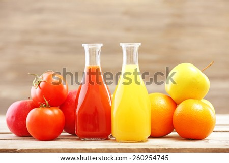 Glass bottles of fresh healthy juice with set of fruits and vegetables on wooden background