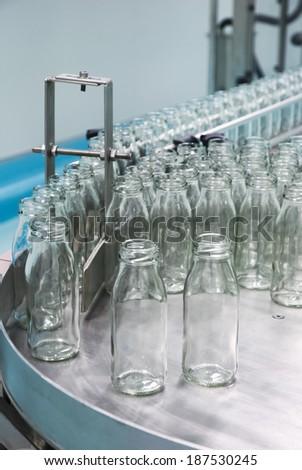 Glass bottles on the conveyor belt - stock photo