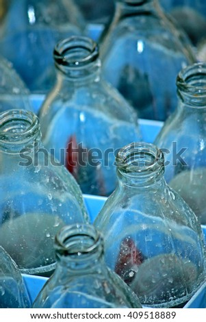 Glass bottles waiting for reuse in blue plastic crate - stock photo