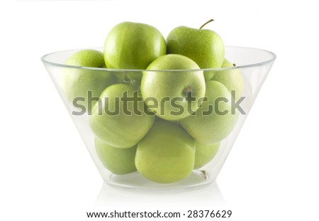 Glass bowl filled with green apples, isolated on white. - stock photo
