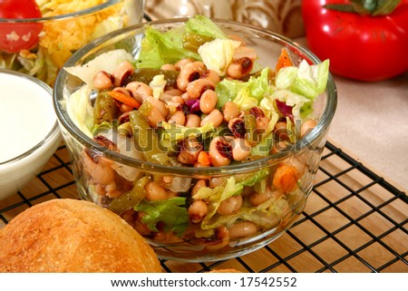 Glass bowl of black eye pea salad in kitchen or restaurant. - stock photo