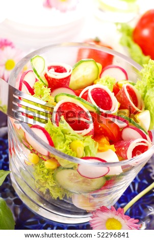 glass bowl of fresh salad with salami,eggs and vegetables
