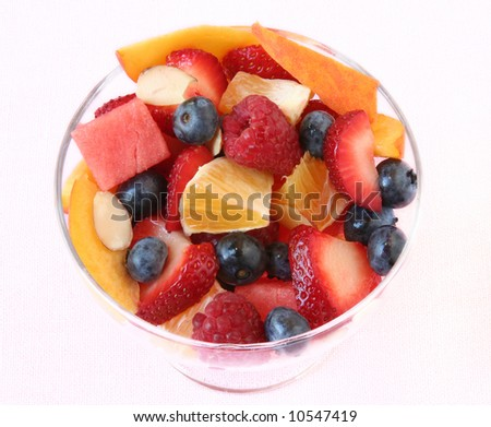 Glass bowl of fruit salad on a white linen tablecloth - stock photo