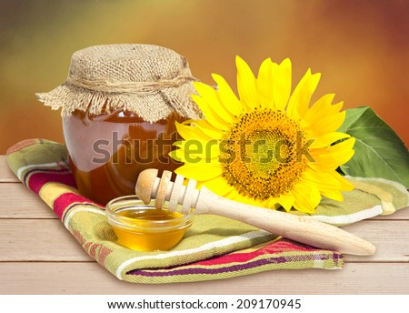 Glass bowl of honey with sunflower on wooden table.