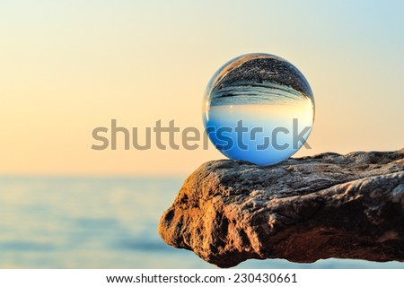 Glass bowl on the boulder at the sea - stock photo