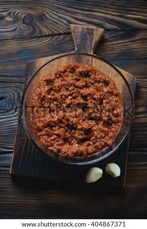 Glass bowl with bolognese sauce in a rustic wooden setting, top view - stock photo
