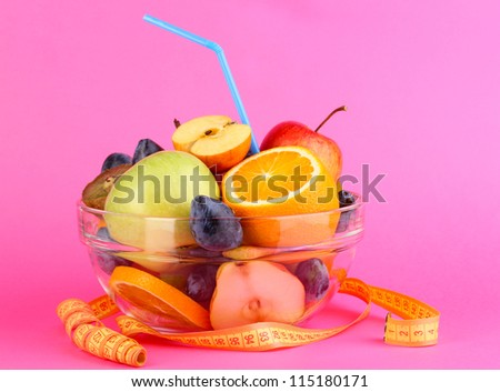 Glass bowl with fruit for diet and measuring tape on pink background - stock photo