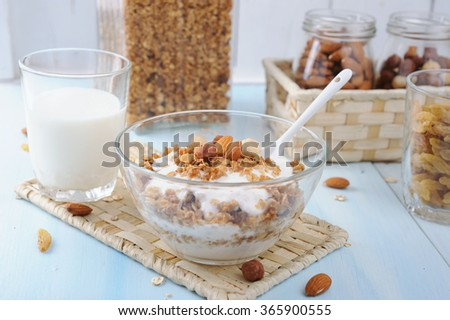 Glass bowl with homemade yogurt and granola from several types of cereals with nuts,coconut chips and dried cranberry
