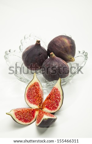 glass bowl with three fresh figs isolated on white background with the foreground a fig cut in four