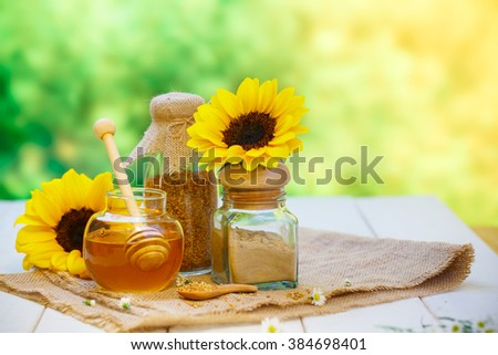 Glass bowls with honey another with pollen and propolis. Honey dipper, spoon, beeswax, sunflower on the wooden 