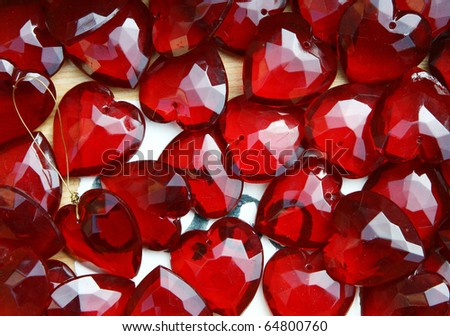 Glass  bright red pendants and brooches in the form of hearts on a street market table. Good for background. - stock photo
