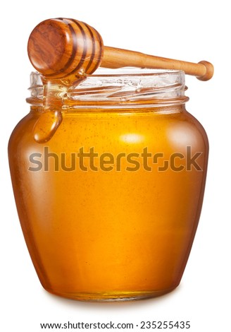 Glass can full of honey and wooden stick on it. Clipping paths. - stock photo