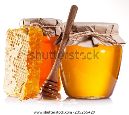 Glass cans full of honey, honeycombs and wooden stick on white background. - stock photo