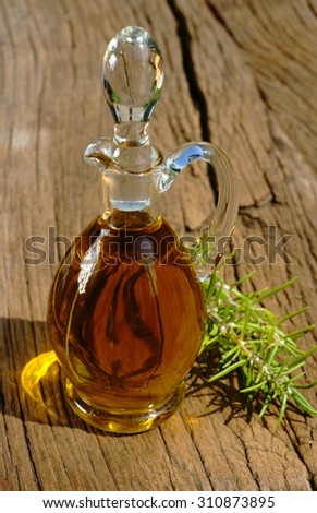 Glass carafe with golden olive oil and a rosemary twig on rustic wooden table - stock photo