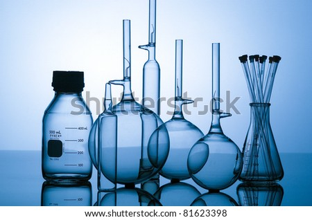 Glass chemical lab bottles shot on glass with blue light - stock photo