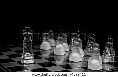 Glass chess pawns in order ,against the king - stock photo