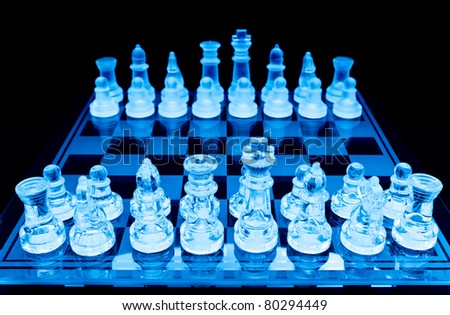 glass chess pieces before the game blue toned - stock photo