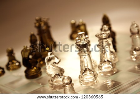 Glass chess pieces on board - stock photo