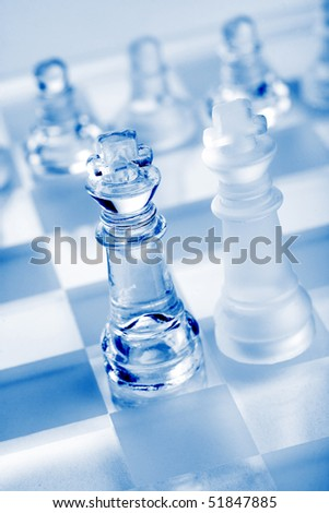 glass chess pieces with blue light - stock photo