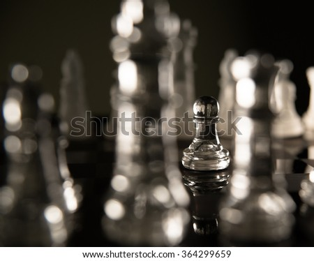 Glass chess set. A pawn makes the first move in a chess game - stock photo