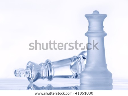 Glass chessmen on a smooth surface light background - stock photo