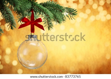 Glass Christmas ball hanging on pine branches with festive background. - stock photo