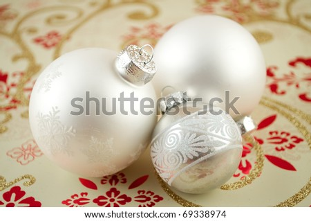 Glass christmas ornaments with snowflakes on wrapping paper - stock photo