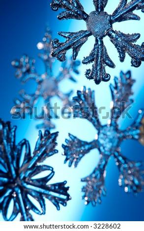 Glass Christmas snow flake ornaments shot on a blue illuminated background - stock photo