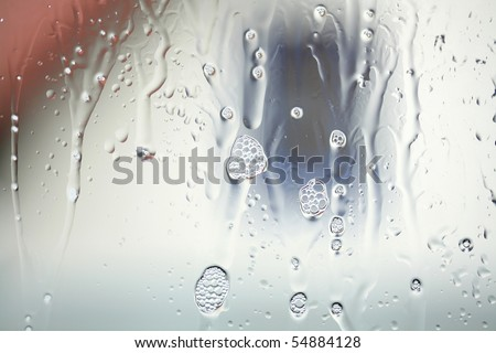 glass cleaner on a sheet of glass in front of a house - stock photo