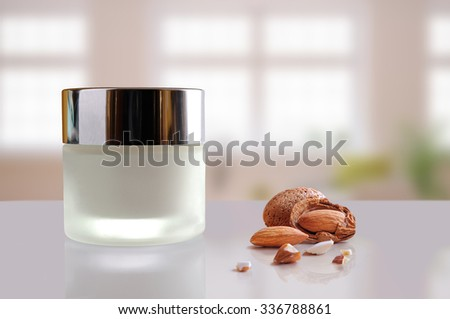 Glass closed jar with facial or body almond moisturizer cream on white table. Front view. Horizontal composition. Windows background. - stock photo
