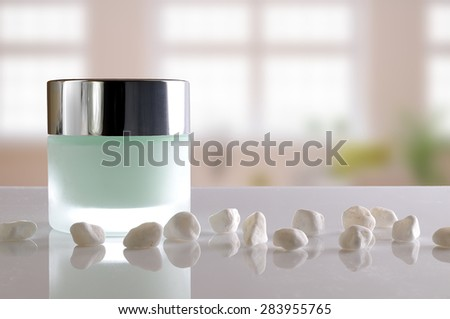 Glass closed jar with facial or body cream on white table with small white stones. Front view. Windows background. - stock photo