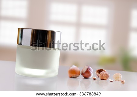 Glass closed jar with facial or body hazelnuts moisturizer on white table. Front view. Horizontal and diagonal composition. Windows background. - stock photo