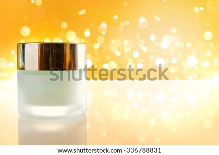 Glass closed jar with facial or body moisturizer on white table. Front view. Horizontal composition. Yellow bokeh background. - stock photo