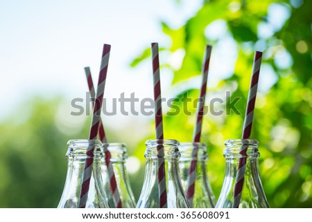 Glass cocktail bottles with straws over the green sunny background