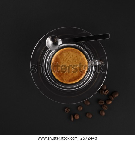 glass coffee cup with fresh made espresso (black background) - stock photo