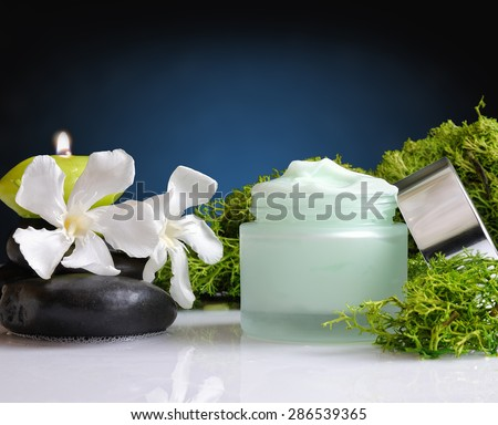 Glass cream jar open algae. Flowers, black stones and seaweed decoration. Windows background. Front view - stock photo