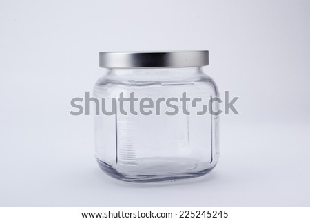 Glass culinary bank with metal lid on a white background.