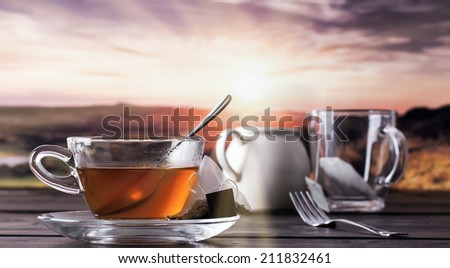 Glass cup and saucer with teabag on a table with a view of the sunset