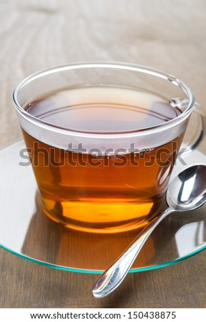 Glass cup of black tea on wooden background, close-up, vertical