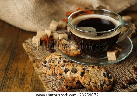 Glass cup of coffee and tasty cookie on wooden background - stock photo