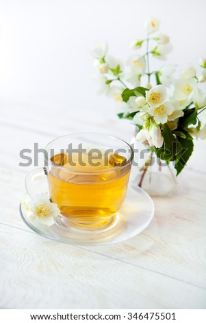 glass cup of green tea with bouquet of jasmine on a white background wooden table. - stock photo