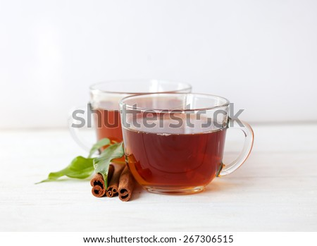 Glass cup of green tea with cinnamon sticks on wooden table background. - stock photo
