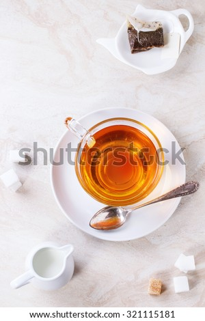 Glass cup of hot tea on saucer with sugar cubes, jug of milk and tea bag over white marble backgtound. Top view - stock photo