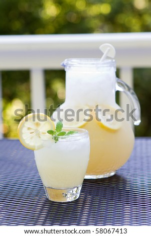 Glass cup of lemonade with ice, sprig of mint and crushed ice and pitcher behind with lemon slices and crushed ice inside.  Selective focus on the glass cup.