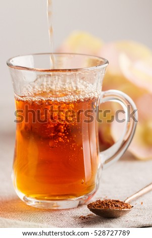 Glass cup of rooibos tea. Shallow focus