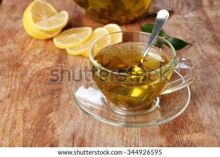 Glass cup of tea and teapot on wooden background decorated with sliced lemon and green leaves, close up
