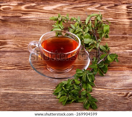 Glass cup of tea on a wooden table with  and mint leaves.