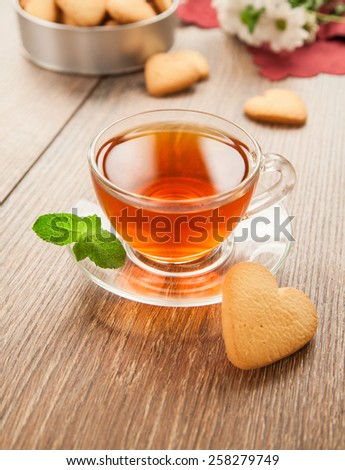 Glass cup of tea on a wooden table with flowers and a box of cookies. - stock photo