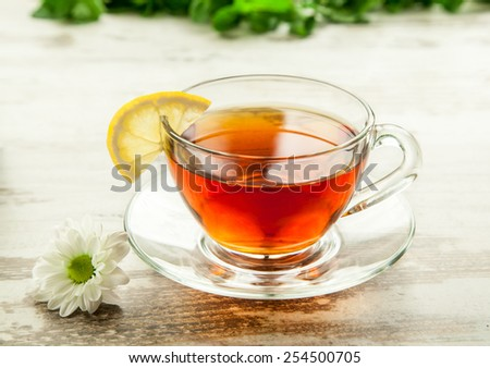 Glass cup of tea on a wooden table with lemon and flower. - stock photo